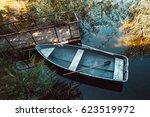 Old Boat With Oar Near Wooden...