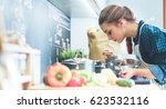 young woman cooking in her... | Shutterstock . vector #623532116
