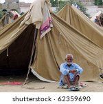 Small photo of KARACHI, PAKISTAN, OCT 03: Flood affectee aged man sits at his make-shift tent house thinks about future at relief camp established at Hawks Bay area on October 3, 2010 in Karachi, Pakistan.