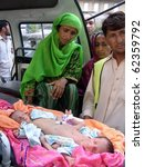 Small photo of KARACHI, PAKISTAN, OCT 02: Karim Bibi a flood affectee from Thatta area sadly looks her conjoined twin babies after doctors allegedly refused their treatment at Jinnah hospital in Karachi on October 2, 2010 in Karachi, Pakistan.