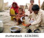 Small photo of KARACHI, PAKISTAN, OCT 03: Flood affectee child serves tea to his family members at their make-shift tent house at relief camp established at Hawks Bay area on October 3, 2010 in Karachi, Pakistan.