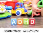 Small photo of Attention Deficit Hyperactivity Disorder or ADHD concept with toddler hand touching colored cubes against toys