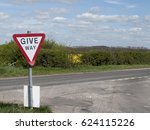 Small photo of West Tytherley, Hampshire, England - April 18, 2017: Give way traffic sign on T junction of single lane country track with main road