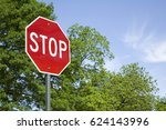 Small photo of A stop sign against green trees and blue sky in full sun. A horizontal format with the stop sign in the left third of the frame, leaving room for copy to the right.