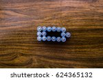Small photo of Alkaline batteries in the form of a battery charge on a wooden background. Charging mobile devices. Energy.