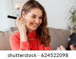 Small photo of beauty, makeup, cosmetics and people concept - happy smiling young woman with brush applying bronzer or blush to her face and looking to mirror at home