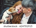 Stock photo a man and a woman are walking around the city they are holding a dog jack is scattered in his arms 624701915