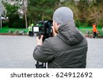 Small photo of Video maker with camera shoots a news story, view from back side, a white clean LCD screen on the video camera, cold weather, a park area.