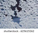 Small photo of Snow adhered to the window glass. Abstract winter background.