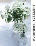 Small photo of Spiraea vanhouttei. Spiraea Flowers in a Glas Vase on a Table in a Garden. Spiraea Flowers Bouquet.