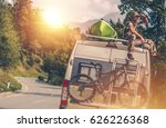 The Ultimate RV Vacation. Camper Van Traveling with Kayak and Mountain Bike. Relaxing Men Seating on the Motorhome Roof. - stock photo