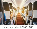 Small photo of passenger seat, Interior of airplane with passengers sitting on seats and stewardess walking the aisle in background. Travel concept,vintage color,selective focus