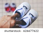 a father holding a pair of shoe ... | Shutterstock . vector #626677622