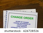 Small photo of Change order concept with blueprints in a wood texture background.