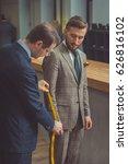 tailor measures a man in studio | Shutterstock . vector #626816102
