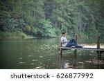 single man listen music on dock | Shutterstock . vector #626877992