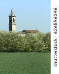 Small photo of Babina (Pc), Italy, the bell tower of a church with some acacia plants in April