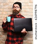 Small photo of Bearded man, long beard. Brutal caucasian surprised unshaven hipster holding laptop with mag or cup in red black checkered shirt with hat and glasses on beige brick wall studio background