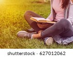 young girl reading book outside ... | Shutterstock . vector #627012062