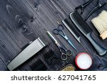Small photo of Hairdresser tools on wooden background. Top view on wooden table with scissors, comb, hairbrushes and hairclips, free space. Barbershop, manhood concept
