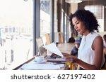 businesswoman by window working ... | Shutterstock . vector #627197402