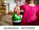 little girl putting used... | Shutterstock . vector #627223322