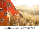 Small photo of African woman in traditional clothes walking with her hand touching field of barley or wheat crops at sunset or sunrise