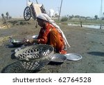 Small photo of GARHI KHUDA BAKHSH, PAKISTAN - OCT 09: Flood affectee girl washes cooking utensils at flood affectees relief camp established on October 09, 2010 in Garhi Khuda Bux, Pakistan.