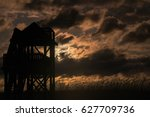 Small photo of observation tower with incredible sun rays abd clouds