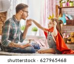 Small photo of Funny time! Father and his child are playing at home. Cute girl holding paper crown on stick and pretend of princess. Dad kisses hand of his daughter. Family holiday and togetherness.
