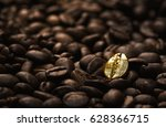 Individuality, standing out  from a crowd concept, close up of a single bright, gold coffee bean over many dark ones with copy space - stock photo