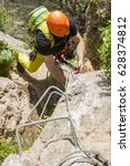 Small photo of From above shot of alpinist clinging rock and climbing up
