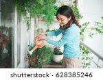 Woman Wtering Plant In...