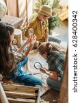 Small photo of cute kids playing treasure hunt with map on porch