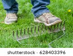 Small photo of A man stepping accidentally on a rake