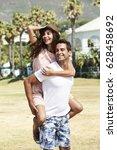 loving couple piggyback in park | Shutterstock . vector #628458692