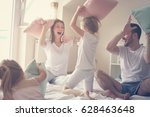 Stock photo family having funny pillow fight on bed parents spending free time with their daughters 628463648