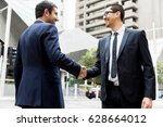two businessmen shaking their... | Shutterstock . vector #628664012