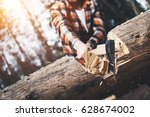 Small photo of Strong logger in a plaid shirt chopping a big tree. Wood chips fly apart