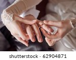 bride putting a ring on groom's ... | Shutterstock . vector #62904871