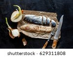 Stock photo herring fillet marinated spices knife onion on a dark metal table view from above russian 629311808