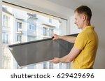 man is holding fabric window... | Shutterstock . vector #629429696