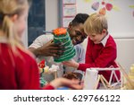 young teacher is helping one of ... | Shutterstock . vector #629766122