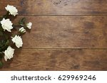 Stock photo white roses on rustic wood background 629969246