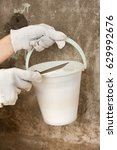 Small photo of hands of plasterer holding bucket with plaster and spatula on the concrete wall background