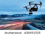 drone quad copter with a camera flies over a road with car lights - stock photo