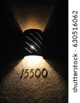 Small photo of Adobe house numbers lit up by copper sconce lantern in Tucson, Arizona