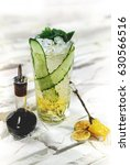 Small photo of Bright green alcohol cocktail with cucumber garnish with honey and angostura on white background