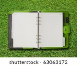 Open Green Cover Binder on Green Grass Background - stock photo