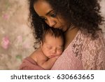 Stock photo beautiful african mother in pink lace dress holding her week old little baby 630663665